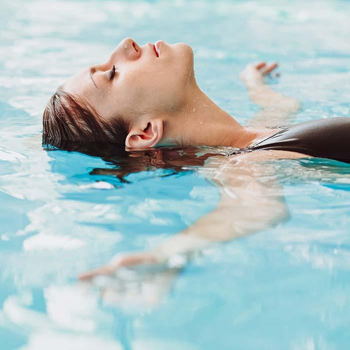 Frau laesst sich entspannt im Wasser treiben