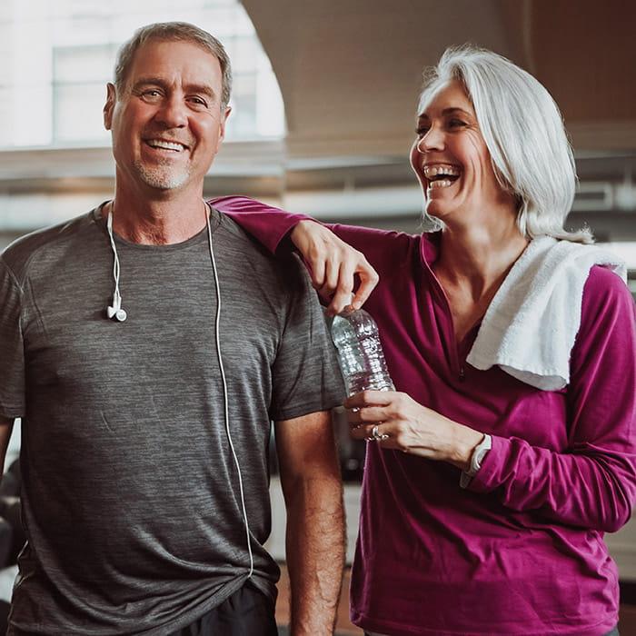 Glückliches Ehepaar trainiert gemeinsam im Fitnessstudio Verso