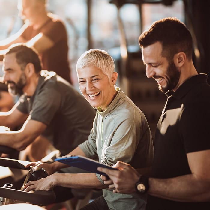 Lachende ältere Frau auf dem Ergometer mit Fitnesstrainer